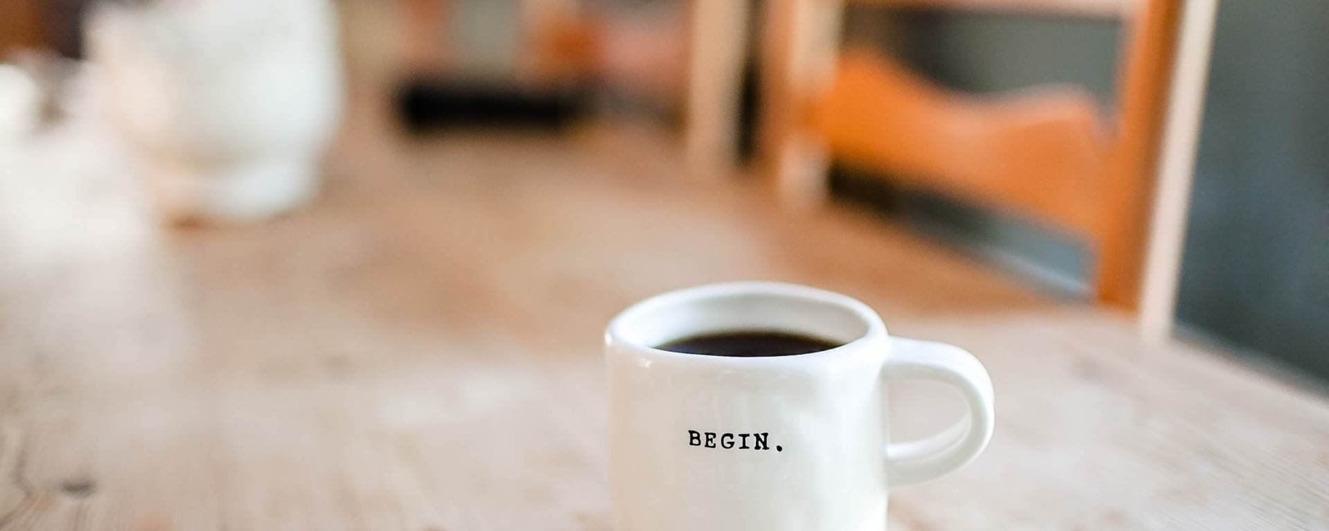 A coffee mug that says Begin. on a table