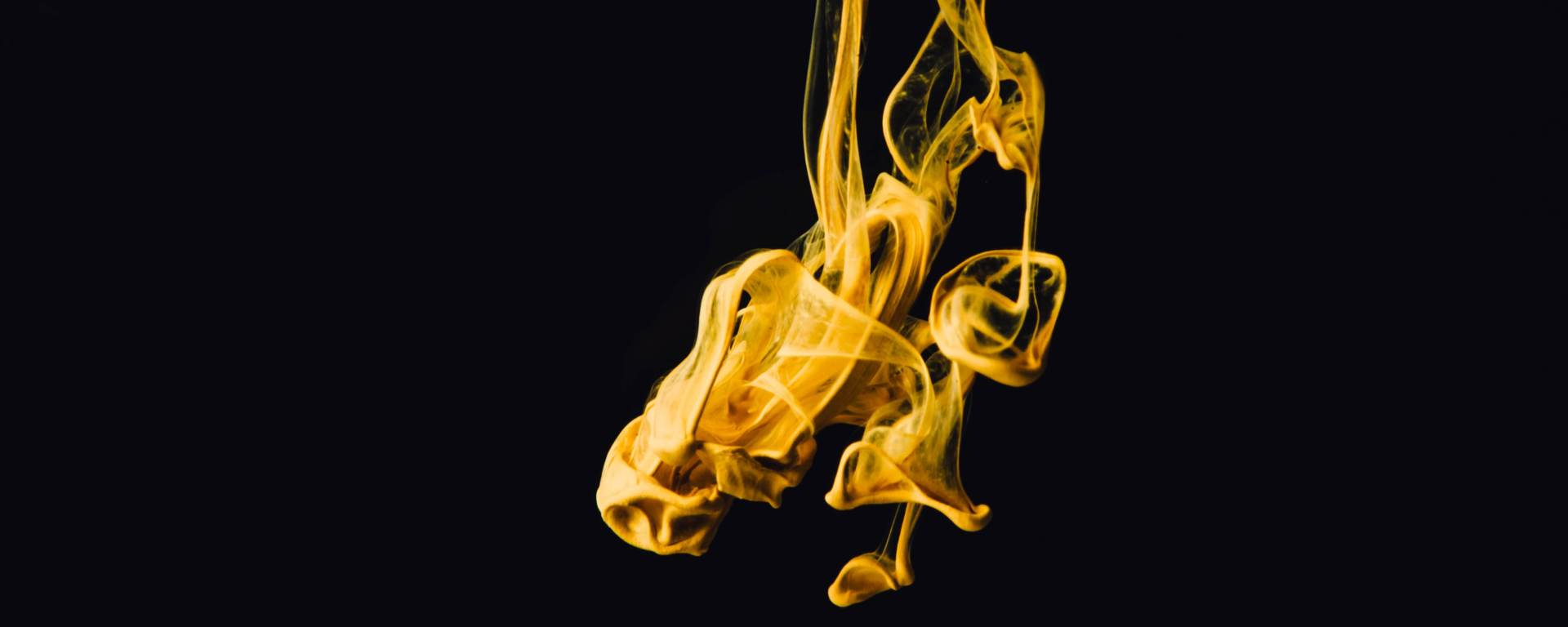 A spool of gold color against a black backdrop